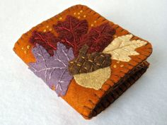 Perfect for fall giving, this deep copper wool blend felt needle book is embellished with three fall leaves and an acorn on its front cover.