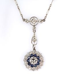 This gorgeous Art Deco Necklace features a nearly one carat old European Cut center diamond surrounded by a halo of round cut Sapphires and a second halo of old European cut diamonds all set in a hand