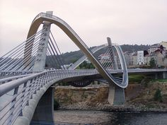 The most distinctive feature of the Millennium Bridge in Ourense - technically a cable-stayed bridge - is the pedestrian walkway that swirls ethereally around the pylons like a serpentine, and whose slopes reach an inclination of 67 degrees. Bridges Architecture, Modern Architecture, Cable Stayed Bridge, Millennium Bridge, Famous Bridges, Bridge Design, Pedestrian Bridge, Suspension Bridge, Spain And Portugal