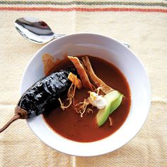 The heat of this deep-red ancho chile soup and its pasilla chile garnish is balanced by the addition of cooling crema and thinly sliced avocado.
