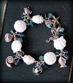 Seaside charm bracelet by Cindy Wimmer with lampwork beads by Shannon Westmeyer - full of Swarovski crystals and sterling silver ocean charms.  cindywimmer.com