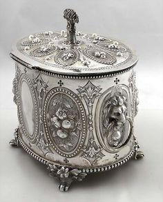 English Sterling Double Biscuit Box by Charles Boynton 1868  A large heavy oval English silver biscuit box on four feet with medallions around the body and hinged lid, the center of each chased with flowers. There are lion masks with rings on each side of the box, there is a central divider inside and the finial is in the form of a sheaf of wheat with a scythe. The front medallion is engraved with a crest of Insole of Ely Court, Glamorganshire. Dated for London 1868 maker Charles Boynton