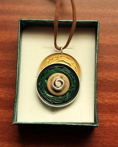 Colgante realizado con Cápsulas Nespresso recicladas, botones de varios colores y abalorios a juego, forrado en la parte posterior con fieltro. Incluye cordón y cierre metalico.