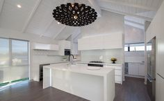 A massive kitchen and scullery running along behind. With the addition of a centre piece light shade by David Trubridge.