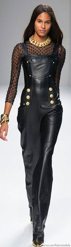 Black faux leather Balmain jumper worn about over sheer black top. Jumper features gold button and the outfit is accessorised with a chunky gold chain necklace and gold cuff bracelet.. DIY the look yourself: http://mjtrends.com/pins.php?name=faux-leather-for-jumper