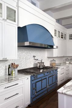 White and blue kitchen features white shaker cabinets adorned with glass knobs paired with gray and white marble countertops and a silver iridescent tile backsplash.