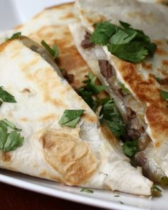 Servings: 2 quesadillasINGREDIENTS1 tablespoon olive oil½ pound skirt steak, sliced into thin stripsSalt, to tastePepper, to taste¼ cup onion, julienned¼ cup green bell pepper, julienned2 large flour tortillas4 slices provolone cheese (double for 2 quesadillas)GARNISHParsleyCheese saucePREPARATION1. Heat olive oil in a large skillet and add the strips of skirt steak. Season with salt & pepper and cook 5-7 minutes. Remove from the pan.2. Add onion and bell peppers to the pan and cook until…