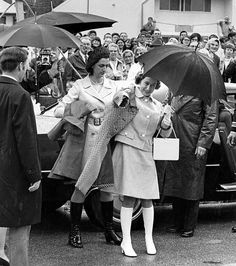 Queen Elizabeth II is helped into her raincoat on arrival at Keewatin Community College. The Pas, Manitoba. July 11, 1970.