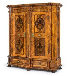 "Baroque hall cupboard, Known as a ""Maria Theresien Schrank"", Austria, mid 18th century. In softwood with walnut veneer, demountable by means of the wedge joints, with a removable cornice and plinth, with canted stepped angles, serpentine front with two doors, marquetry panels and bands in further fine woods such as plum, maple and burlwood, with a matte finish, two plinth drawers, 2-bar box lock and brass mounts."