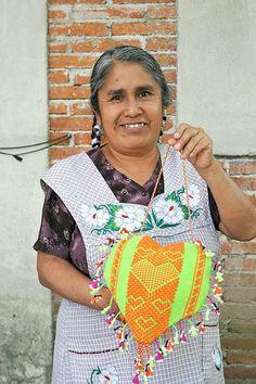 Master weaver Crispina Navarro Gomez shows off a heart shaped textile she made for a special exhibition.  Santo Tomas Jalieza, Oaxaca, Mexico
