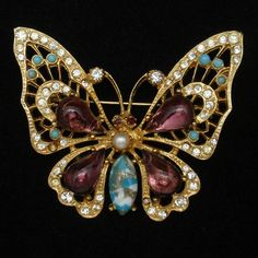 Gold tone butterfly pin set with large purple and art glass stones and accented with smaller rhinestones. The open design is airy and ideal for spring. This butterfly pin is by ART and is hallmarked o