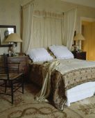 White pillows and patterned throw on antique half tester bed with cream drapes