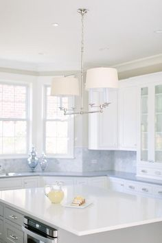 A Classic Billiard Light illuminates a light gray island fitted with polished nickel pulls and a microwave located under a white quartz countertop.