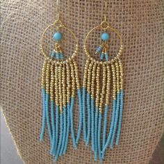 "Boho Tribal Turquoise Beaded Earrings Long enough to dust your collarbone! These earrings are bold, with turquoise colored seed beads combined with gold seed beads creating a bohemian flair. Every last seed bead has been strung by hand and each earring contains 424 beads...yes, I counted. Each earrings is about 4.5 inches long. See more of my handmade jewelry on Etsy. Just search for ""CurlsnPearlsBoutique"" on Etsy.com Thanks for stopping by! Handmade Jewelry Earrings"