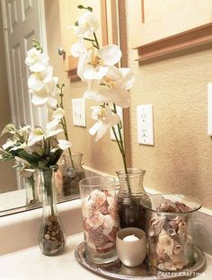chattycrafting.com | Here's a photo of my coastal themed bathroom idea on a tight budget. I think this would be great as apartment/small bathroom decor if you're not into nautical themes, but if you're more of a coastal decorator like me. I like the spa-like vibe. Dollar tree silver tray, seashell vase fillers, river rocks... #dollartree #bathroom #decor
