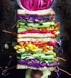 Rainbow sandwich: roasted beet hummus + carrots + curried cauliflower + avocado + tomato + cucumber + lettuce + cabbage + roasted purple sweet potato + super seed bread