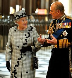 Behind the troops: Queen Elizabeth and the Duke of Edinburgh enter St Paul's for the service honoring the fallen British soldiers in the Iraq war (October 2009).  Queen Elizabeth wears a subtle gray checked suit & hat trimmed with black floral applique, & tiny silver buttons.  Black hat brim; black gloves & bag.  Requisite pearls and brooch.