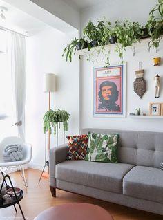 Sala de estar tem piso de madeira, sofá cinza, almofadas estampadas e prateleiras pendentes para colocar plantas.