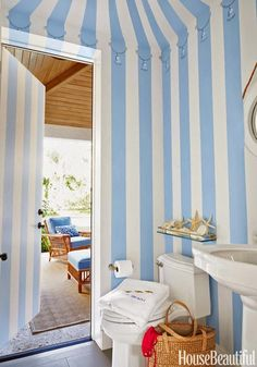 In a Palm Beach house decorated by Mimi McMakin and Ashley Sharpe of Kemble Interiors, a powder room near the pool is painted to look like a cabana with a tasseled, tented awning. Even the door has the striped pattern. Bathroom Color Schemes, Bathroom Paint Colors, Pool House Bathroom, Powder Room Decor, Powder Rooms, Striped Wallpaper, Beach Design, Blue Rooms, New Blue