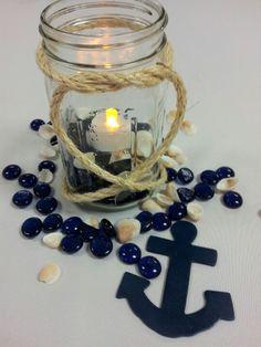 Our homemade nautical centerpieces...mason jar with rope, rocks/shells, and a tea light!