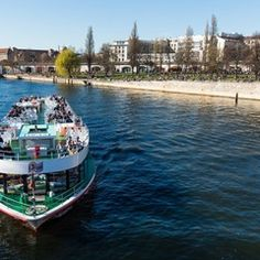 Tourists enjoy the sun on a ship on Spree river in Berlin, Germany