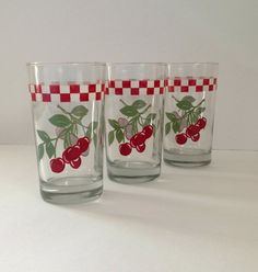 Vintage circa 1960s Anchor Hocking set of three beverage glasses. These glasses are decorated with cherries, and a red and white checkered border.