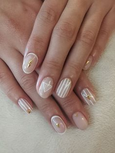 Nude nails with white and gold accents.