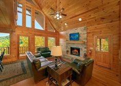 Log cabin living room looking out on mountains with dark furniture