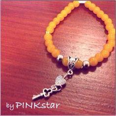 Leuke hippe armband van elastiek met glaskralen mosterd geel, hangertje met hartje en sleuteltje