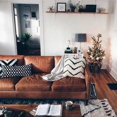 joli salon marocain avec canapé en cuir marron tapis beige parquet en bois foncé