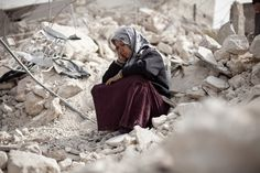 Syrian Zakia Abdullah sits on the rubble of her house in the Tariq al-Bab district of the northern city of Aleppo on February 23, 2013. (Pablo Tosco/AFP/Getty Images)