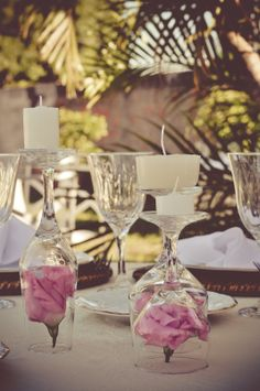 Decoração da mesa dos convidados. Taça virada pra baixo com rosas dentro e vela em cima.