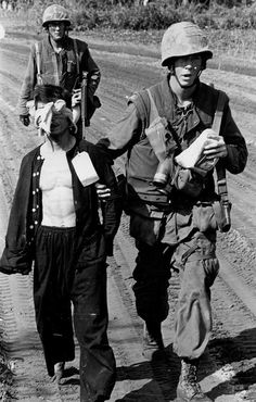 Vietnam War. A Viet Cong prisoner captured during Operation Double Eagle, 20 miles south of Quang Ngai, Vietnam is brought into the collection area by Marines. Prisoners are blindfolded and tied to prevent escape attempts. The card on the prisoner's black pajama shirt relates to circumstances of his capture.
