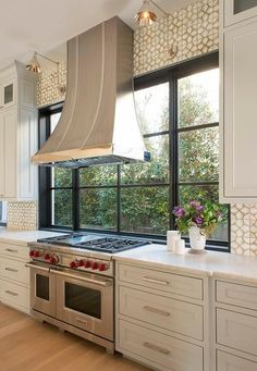 A stainless steel French kitchen hood, illuminated by Boston Functional Library Wall Lights, stand in front of windows and over a Wolf dual range.
