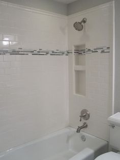Photobucket - tub/shower enclosure with accent band. white subway tiles: Daltile from Home Depot accent tiles: a mix of honed carrara marble, polished Calcutta marble, & aqua/grey sea-glasss from Bedrosian's, Denver location ($10.50/sq ft sheet)