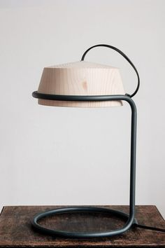 The lamp is small in size, with a clean and contemporary silhouette. It is suitable for a desk or a table. The form resembling a whirligig, allows to adjust the direction of light. The lampshade is made of glued pinewood, shaped on a lathe. The metal … #WoodenLamp