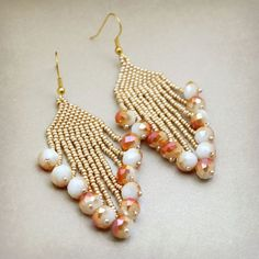 "An eye catching metallic gold seed beaded earring followed by bigger, faceted shiny accent beads below in a splash of peachy tan color on white. Measure 3 1/2"" long, and 1 1/4"" wide, including the 1"""