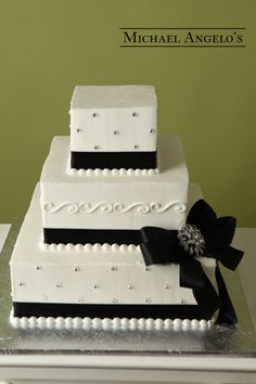 Square Design with Brooch #15Bow This three-tier square buttercream cake is a great size for most weddings.  Each layer is wrapped in satin ribbon, then accented witha a beautiful bow and brooch.  Flowers can be added for another hint of color.  Toppers can be added, but are brought in by the bride and groom.