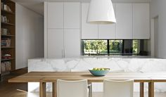 A mirrored splashback brings the outdoors in to a house in Kew, Melbourne.