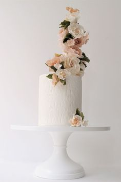 Minimal and beautiful, this white, one tier wedding cake features a tower of pink, handmade sugar flowers.