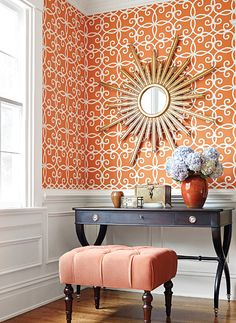 Coppery orange wallpaper with gold sunburst mirror with ebonized x-frame console and tufted velvet ottoman.