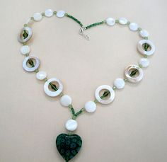 Beautiful glass heart hangs from this stylish necklace. White iridescent shell beads are mixed with green crystal beads. Silver lobster clasp. Necklace is 18 inches, heart and round shell bead hang 2 inches. 100% of profit go to support Mission Trips $28.00