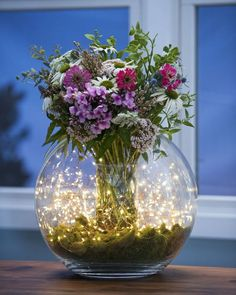 Fairy Lights Cascade Curtain - 10 Strings of Battery Operated Lights. A clever idea to show case Bridesmaids Bouquets and a Guest Table centerpiece.fairy lights but flowers in blues Wedding tables add sea shells sprinkle sea glass around rather than moss