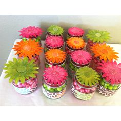 Baby food jars with sixlets, wrappers made from scrapbook paper--- flowers from Hobby Lobby for flair.