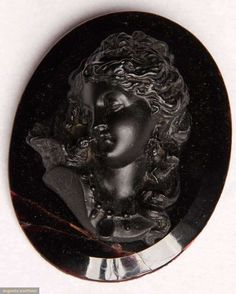 BLACK JET MOURNING CAMEO, 19TH CENTURY Large oval beveled glass base, high relief carved jet bust of woman w/ face turned to dove on her shoulder, 2.25 x 3 inches