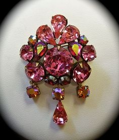 A quality vintage designer rhinestone pin by Regency. Large rhinestones in  round and pear shaped stones in vivid shades of pink are all prong set.
