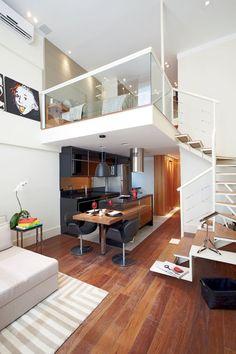 Compact kitchen under the loft platform, next to a passageway and stairs.