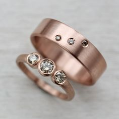 Champagne and Rose Gold | This ring set is in 14k rose gold with C3/C4 Australian champagne diamonds. The women's engagement ring is the Three Stone Ring, and the men's engagement ring is the 6x1.5mm Flat Band and has three diamonds set in the Orion's Belt constellation pattern. Both in 14k rose gold.