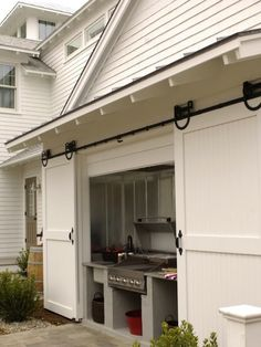 Suzie: Inspiration for Outdoors Spaces - BBQ nook to house your grill with sliding barn doors.