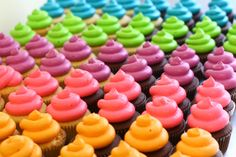 Dozens of neon frosted cupcakes for a kid's graduation party! After testing various brands of food coloring, AmeriColor electric gels created the brightest colors.